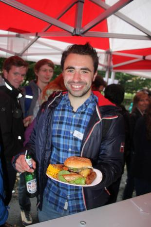 Student with plate of food and a bottle of beer at the event